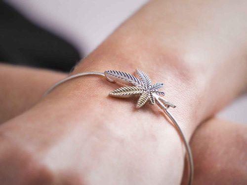 Model wearing silver marijuana leaf arm bracelet