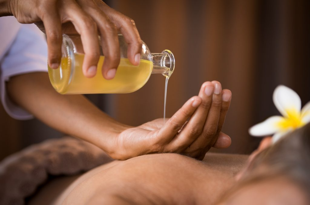 person adding cbd massage oil to their hand