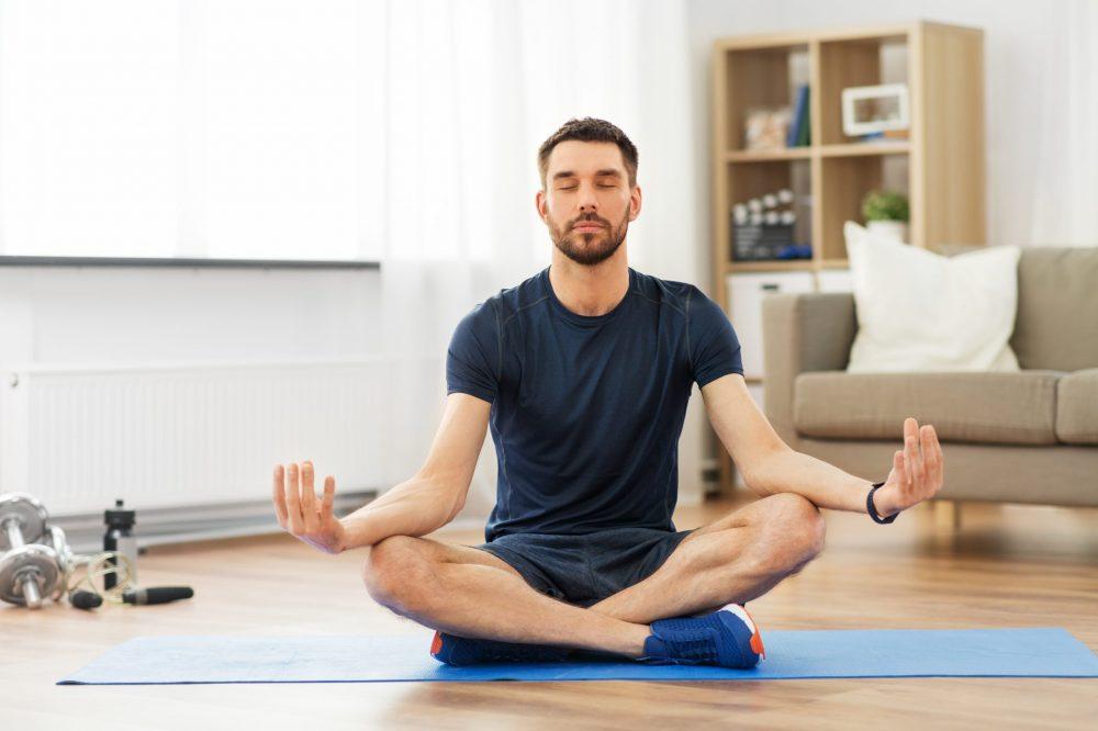man practicing yoga at an at home cannabis retreat